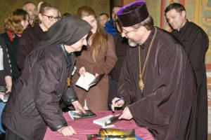 ▲ Владика Святослав Шевчук підписує книжку. Фото Ігоря Юзвяка